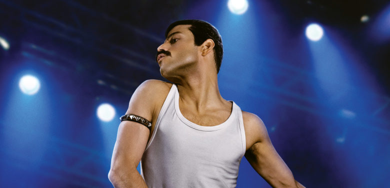 Rami Malek posed as Freddie Mercury in a white tank top and black, spiked armband. He's in front of a blue concert-lit background.