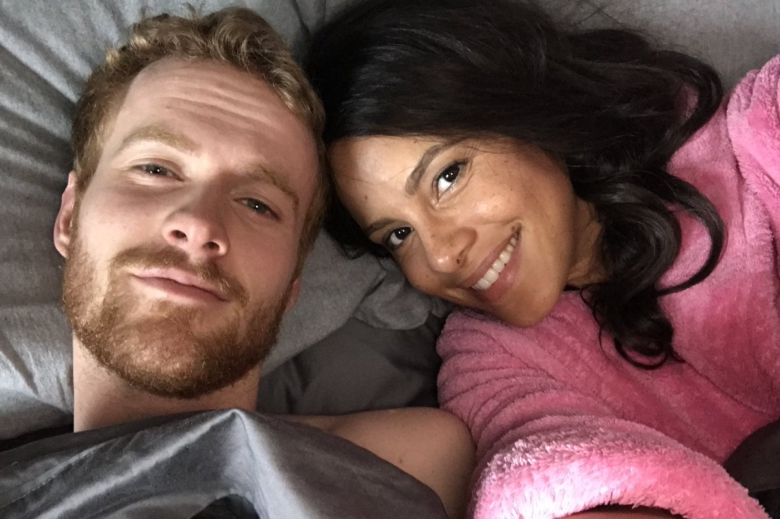 Parisa Fitz-Henley, right, and Murray Fraser take a selfie in costume as Prince Harry and Meghan Markle while lying down on a bed.