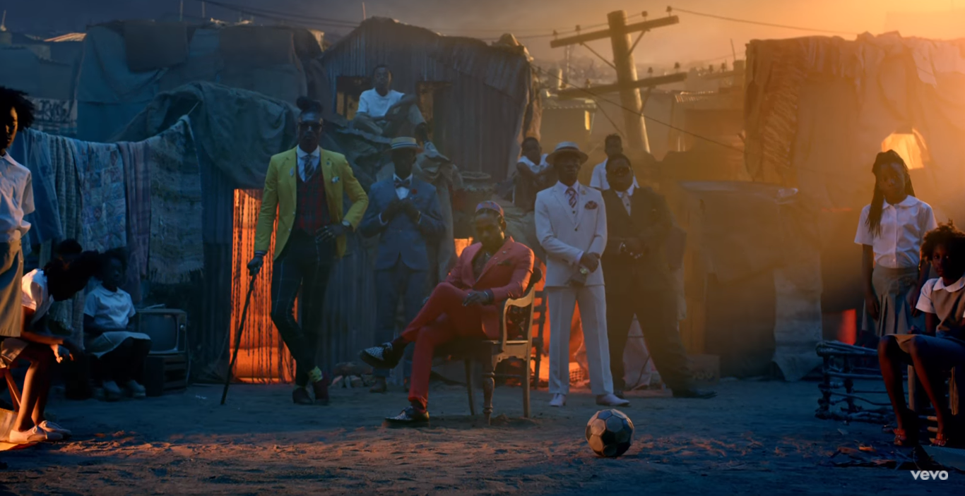 Kendrick Lamar sits in a red tailored suit among brightly-dressed men in a shanty town at sunset.