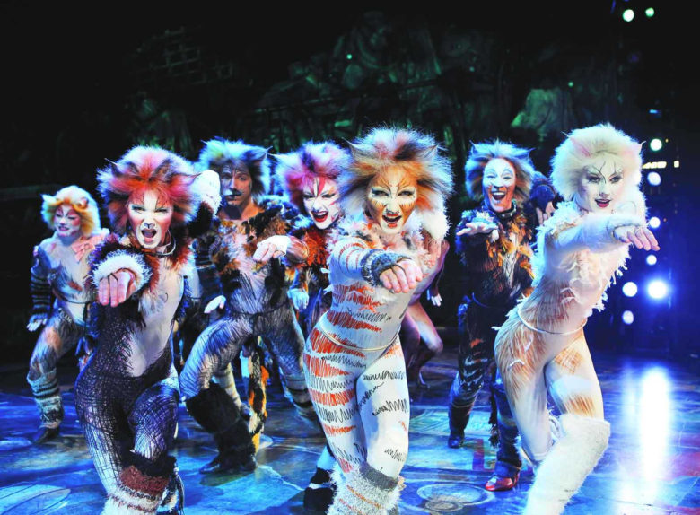 Actors in colorful cat makeup and leotards dance in unison onstage.