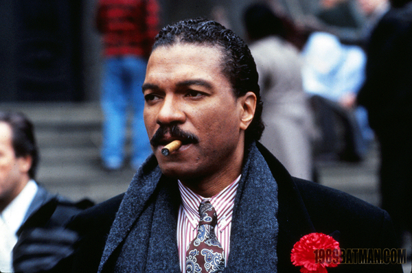 Billie Dee Williams as Harvey Dent is dressed in an expensive coat with red carnation as decoration. He's also wearing a grey scarf, purple and white pinstripe shirt, and purple and blue patterned tie. He has a cigar in his mouth.