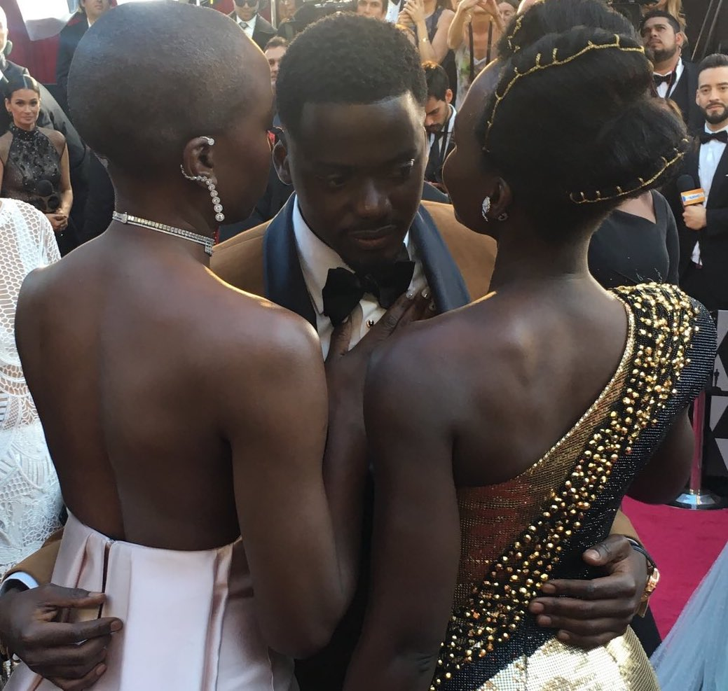 Daniel Kaluuya is embraced by Danai Gurira and Lupita Nyong'o on the red carpet.