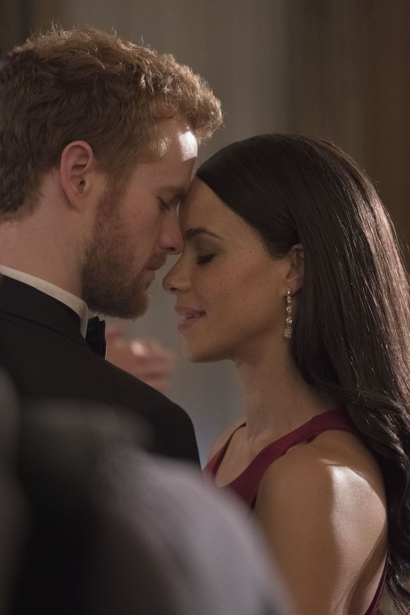 Murray Fraser and Parisa Fitz-Henley as Prince Harry and Meghan Markle, both poshly dressed with eyes closed in a loving embrace.
