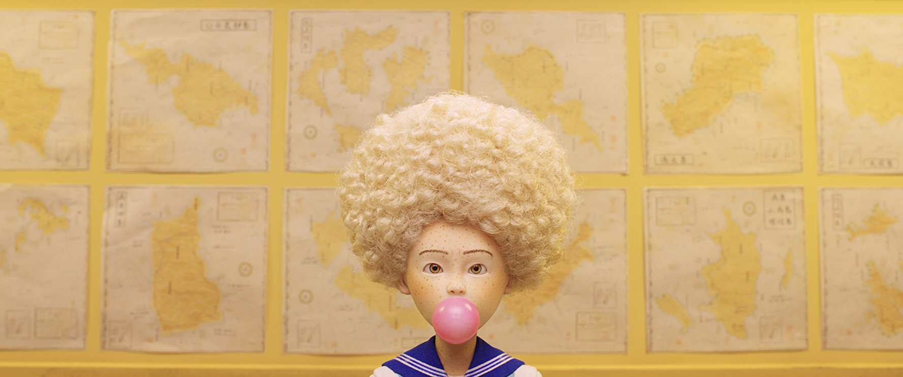 Tracy, voiced by Greta Gerwig, wears an afro and chews pink bubble gum.