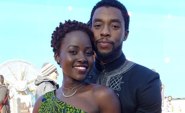 Lupita Nyong'o and Chadwick Boseman pose together in an embrace during a behind-the-scenes moment in Black Panther