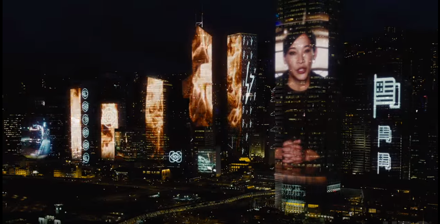 A city at night featuring images of a black woman and a burning fire transposed onto the building faces.