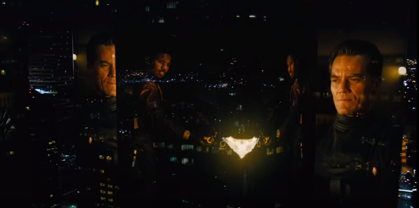 A city at night featuring images of Michael Shannon and Michael B. Jordan transposed onto the building faces. Jordan is shown burning something, probably a bunch of books.