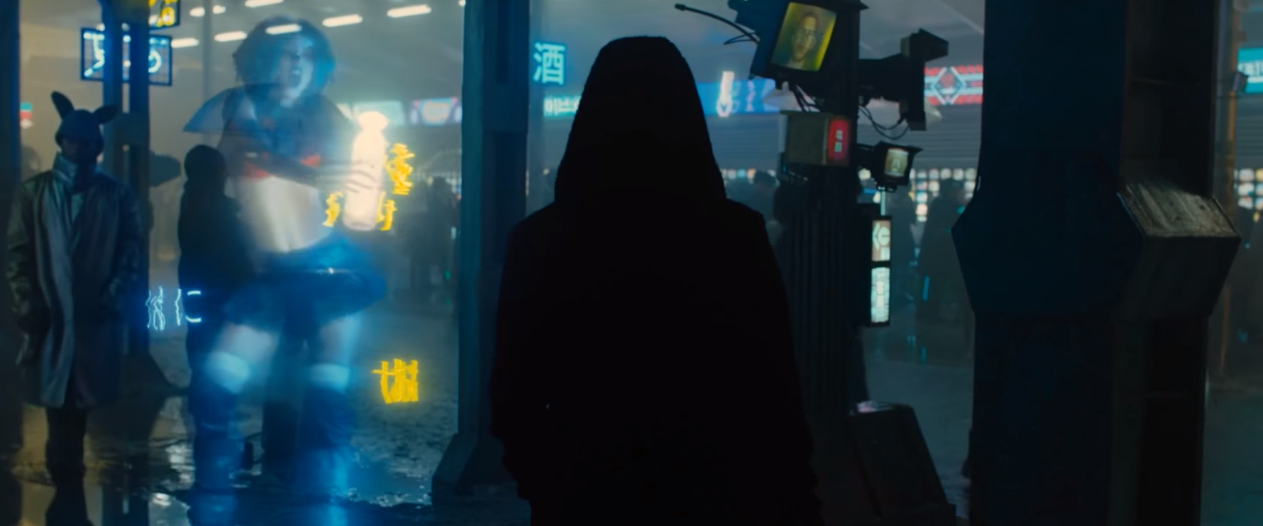 A harajuku girl dances in a hologram as a hooded figure walks by.