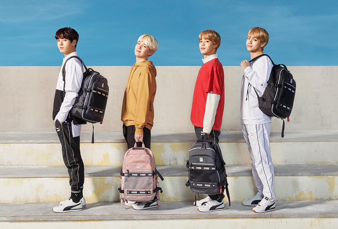 Members of BTS posed near white steps against a blue sky, carrying backpacks from their line.