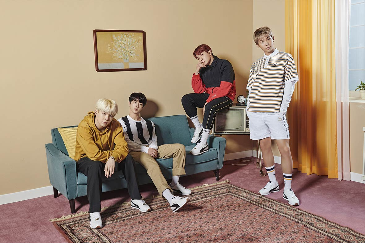 Members of BTS, wearing clothes from their line, posing in a set staged like a living room with a blue couch and faded burgundy rug.