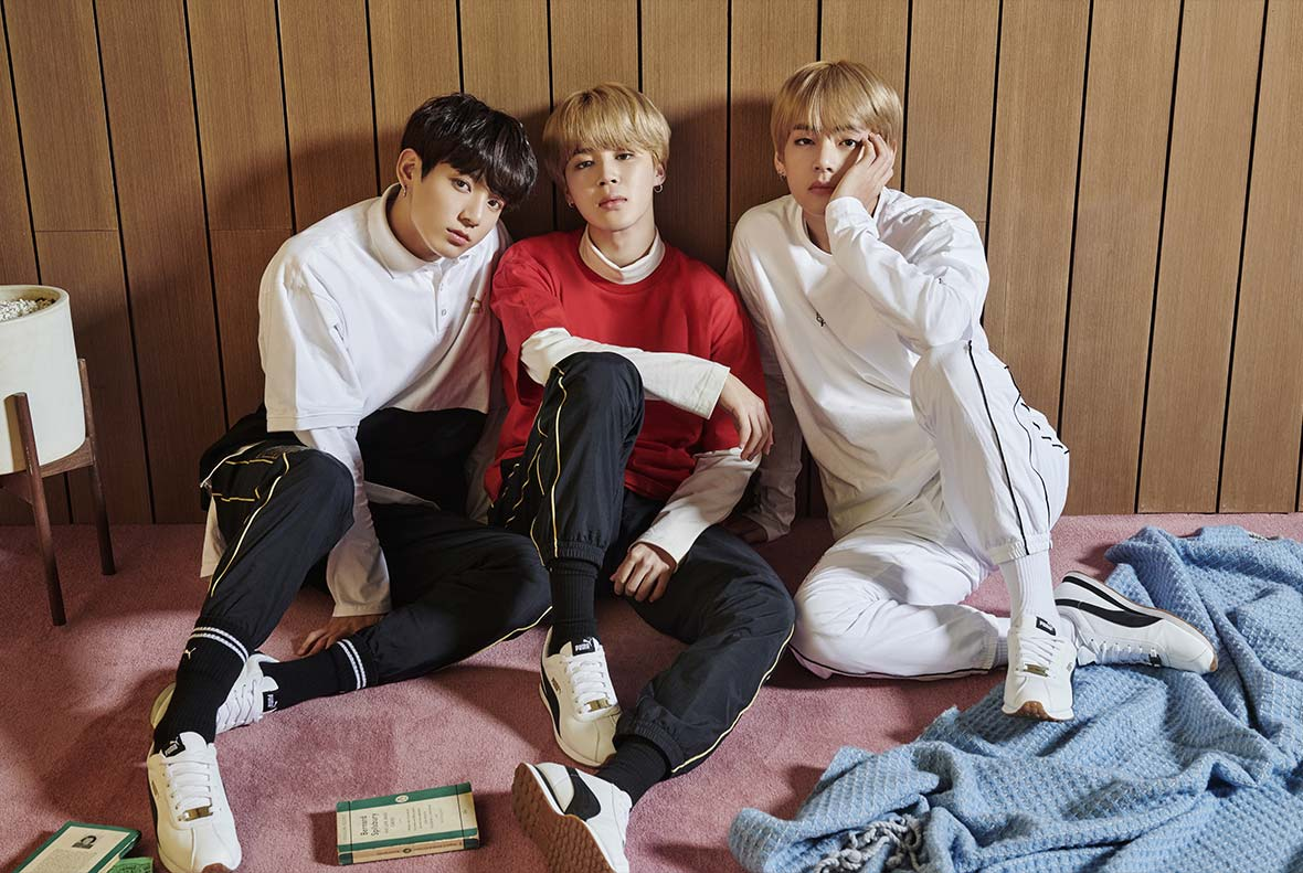 Members of BTS, wearing clothes from their line and sitting against a brown wood-paneled wall, posing in a set staged like a living room.