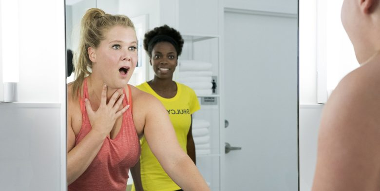 """Amy Schumer reacts to her reflection in the gym bathroom mirror with Sacheer Zamata reacting to Schumer in the background in """"I Feel Pretty"""""""