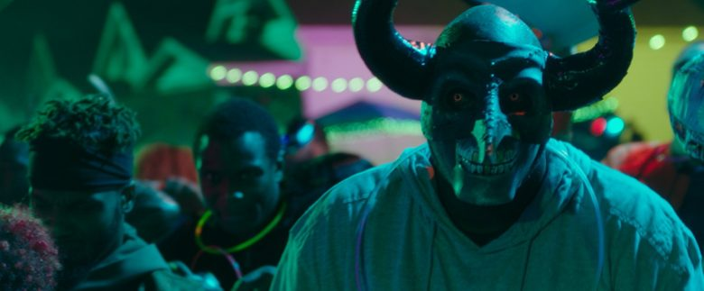 A person in a scary horned mask is in the foreground as black men are possibly partying amid a disturbing color scheme.