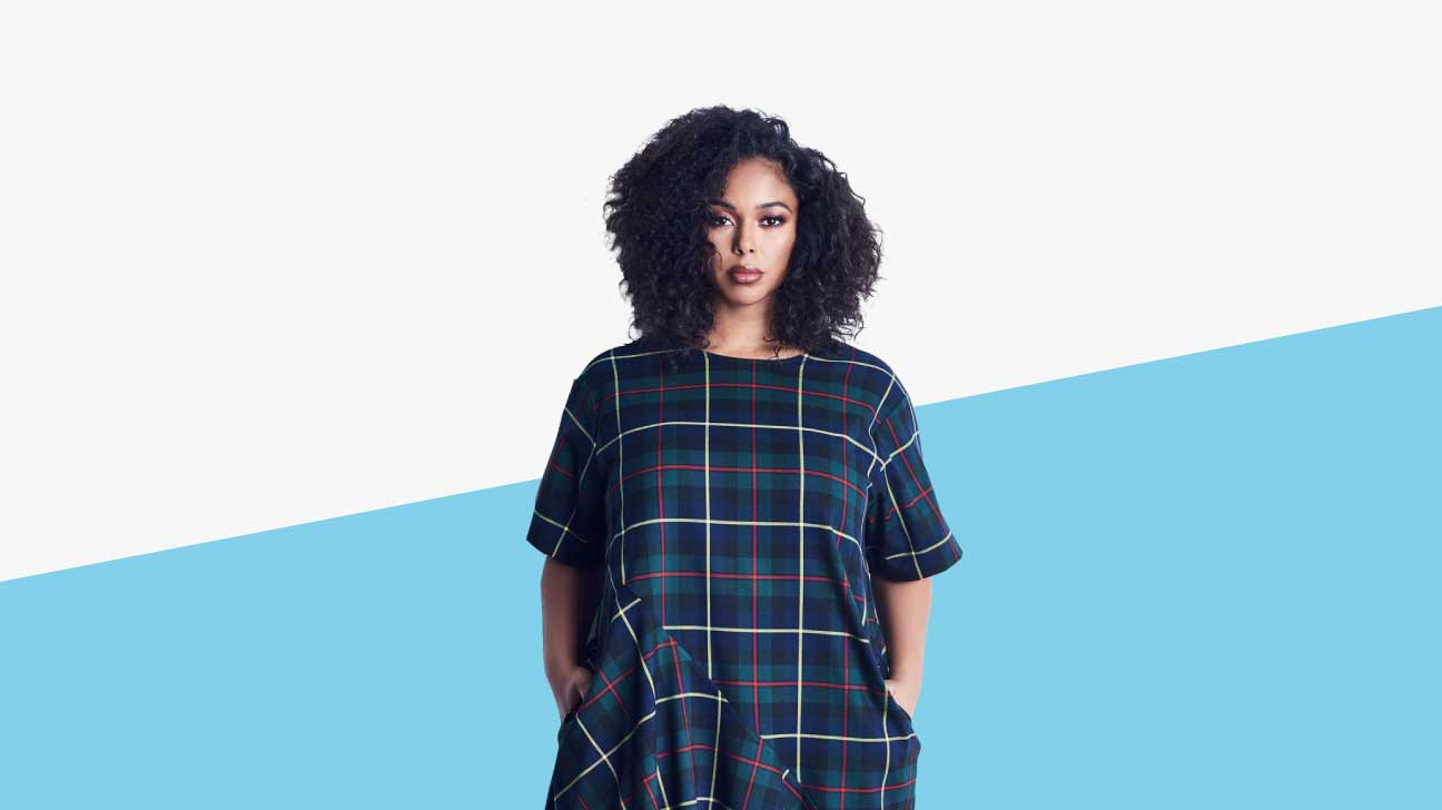 Black plus sized model with curly hair wearing a blue, grey, and forest green large plaid dress
