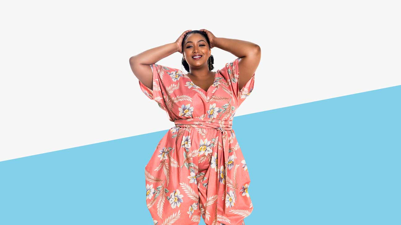 A black plus-sized model is wearing a pink jumpsuit with a white and blue floral print.