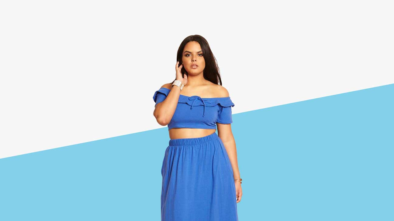 A light-skinned plus sized model is wearing a blue ruffledcropped peasant top and matching skirt set.