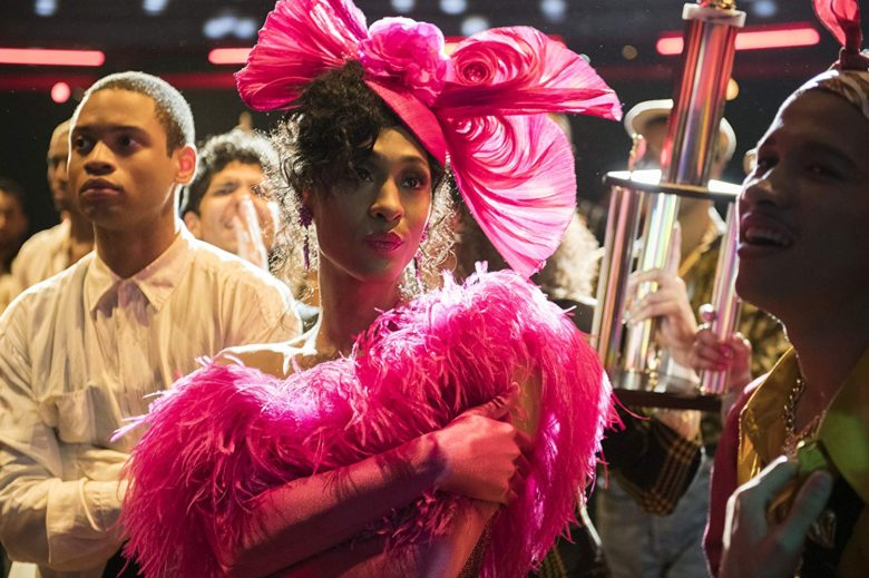 Amid a crowd, Mj Rodriguez, in a feathery pink outfit and wearing a pink hat, holds a trophy after winning a ball category.