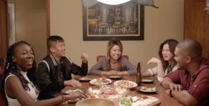 """The cast of """"Do Better"""" sit around the dining room table, laughing and eating dumplings and drinking beer."""