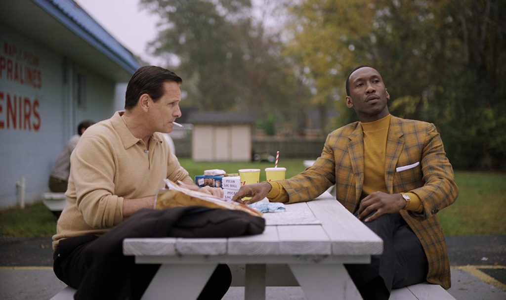 Viggo Mortensen as Tony Lip and Mahershala as Dr. Shirley, sitting at a picnic table eating fast food. Dr. Shirley looks off into the distance as Tony Lip smokes a cigarette.