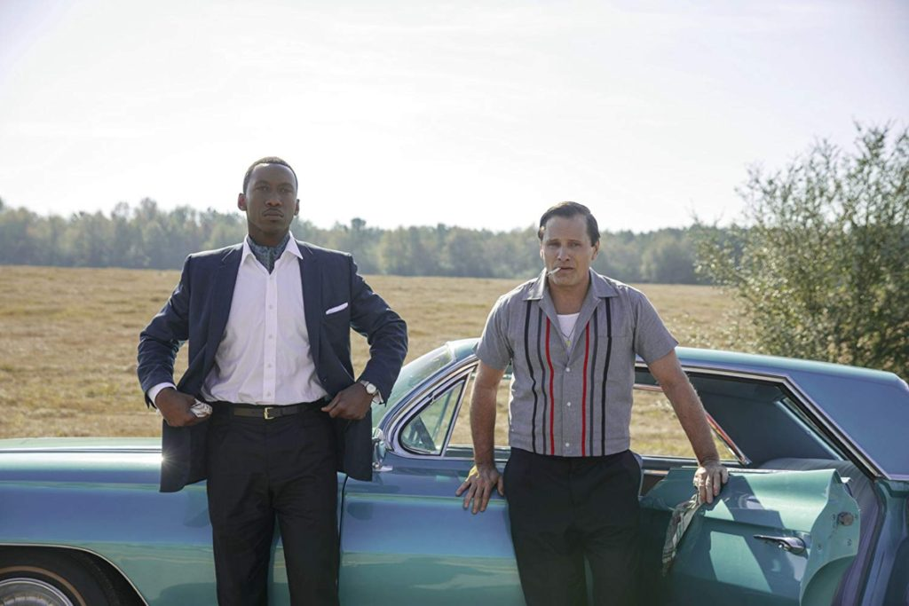Dr. Shirley (Ali) and Tony Lip (Mortensen) standing against Lip's car on the side of the road.
