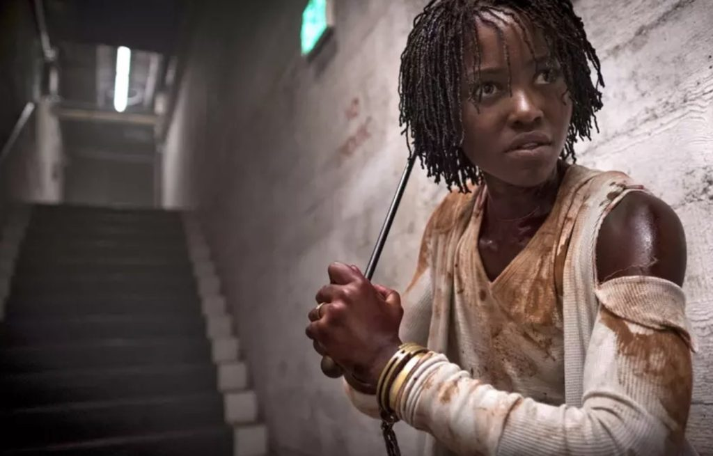 Lupita Nyong'o, bloodied, walks down stairs holding a fire poker.