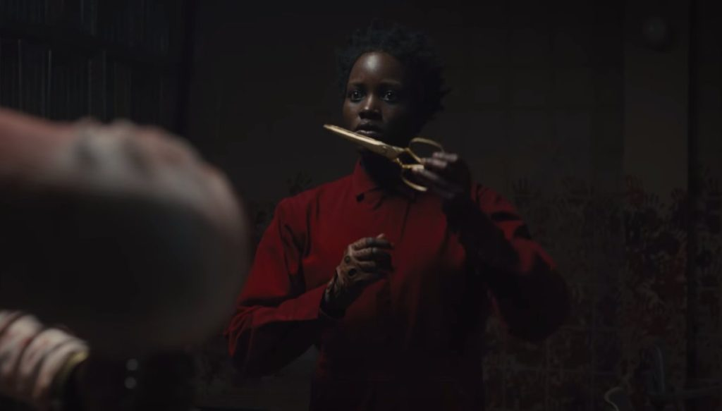 Lupita Nyong'o's evil self, wearing a red jumpsuit and golden scissors