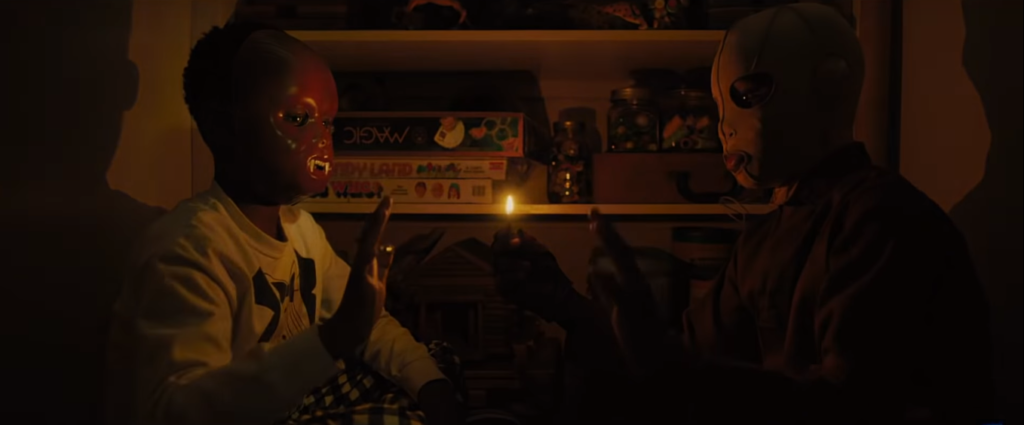 Evan Alex and his doppleganger sit in a flame-lit room. Evan wears a Chewbacca mask and his evil self wears a white mask. Both are holding a hand up to each other.