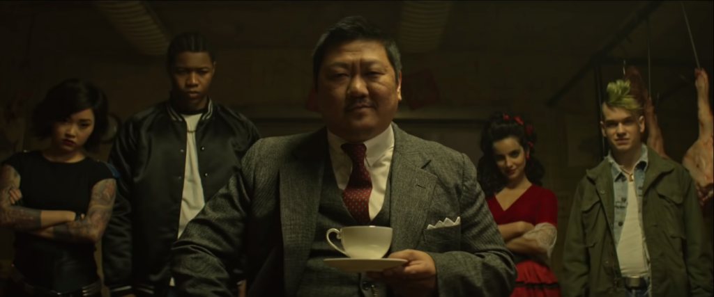 Benedict Wong as the refined Master Lin with Saya, Willie, Maria and Billy (Liam James) in the background. Master Lin sits calmly with his tea cup and saucer. (SyFy/Screencap)