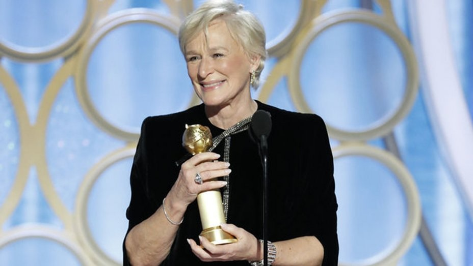 Glenn Close, wearing a black, long sleeved dress, accepts her award with a grateful smile.