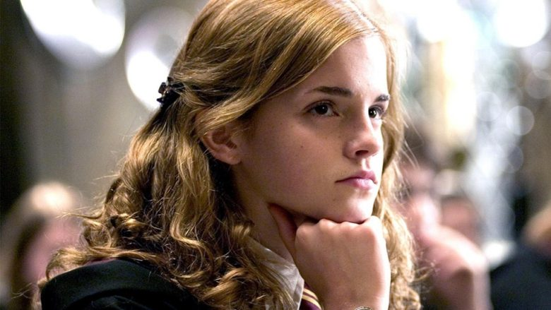 Hermione Granger rests her chin on her closed fits as she looks into the distance while sitting at a table in Hogwarts.