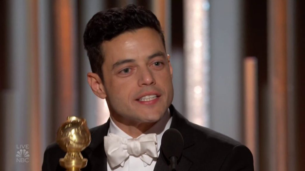Rami Malek in a black tux with white dress shirt and white satin bow time, accepts his award. Of course, he looks dreamy.