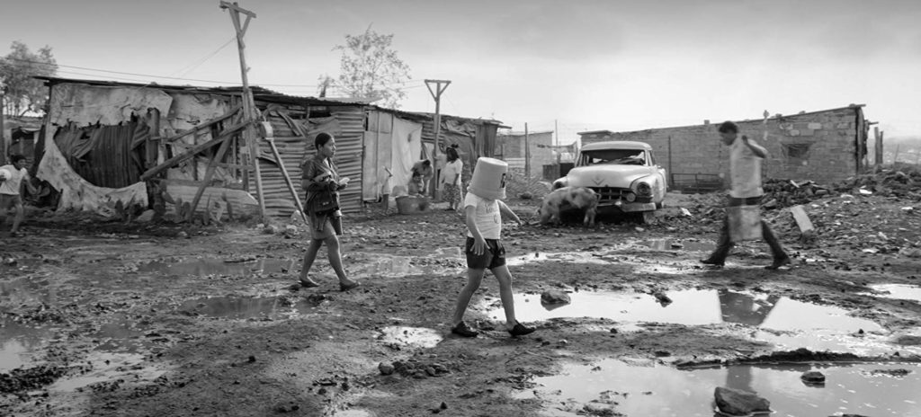In a slum, Cleo walks by a young boy with a bucket on his head, pretending he's an astronaut.
