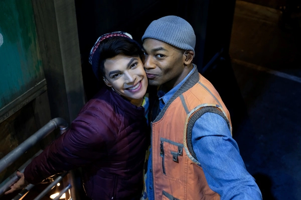 Valentina in boy drag (a maroon puffer coat and maroon an white hat) as Angel and Dixon in a gray ribbed skull cap, orange and grey vest, and blue jean shirt as Tom Collins. Dixon is giving Valentina a peck on the cheek as they pose for the camera.