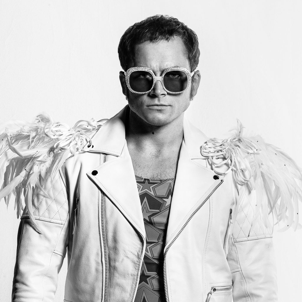 Taron Egerton as Elton John in Rocketman from Paramount Pictures. The black and white picture features Egerton in costume with a white leather jacket with white plumes on the shoulders and large bejeweled sunglasses.