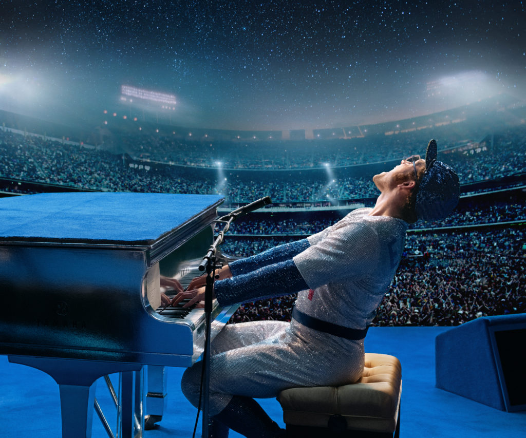 Taron Egerton as Elton John in Rocketman from Paramount Pictures. Elton John is wearing his sequined baseball uniform as he performs to a sold-out crowd.