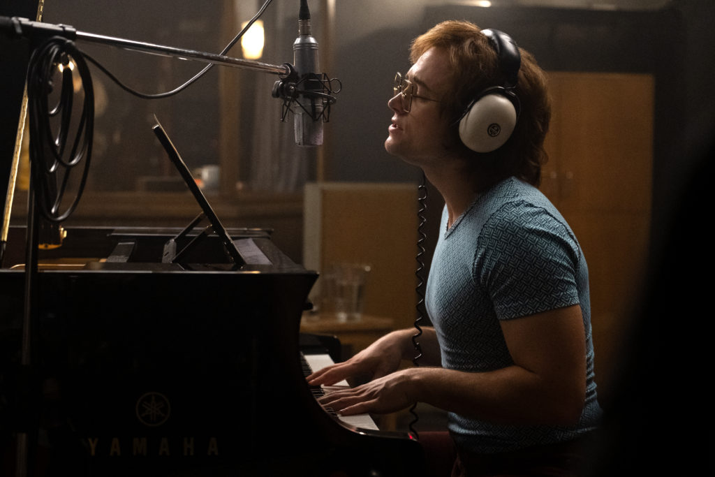 Taron Egerton as Elton John in Rocketman from Paramount Pictures. He's wearing a blue fitted t-shirt and headphones as he records himself playing the piano.