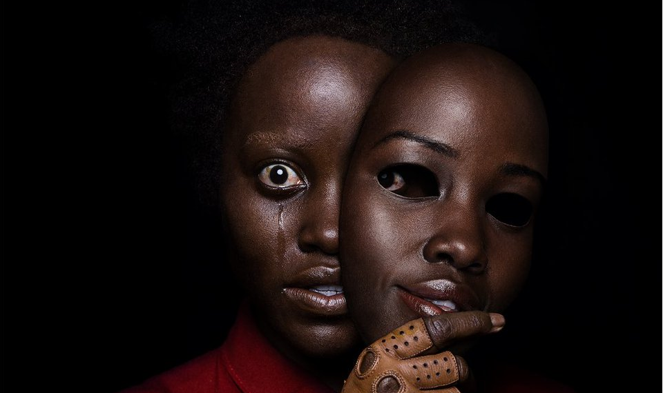 The black poster for US, featuring a crying Lupita Nyong'o as Red holding a mask of Lupita's face. She is wearing a leather glove and a red jumpsuit.