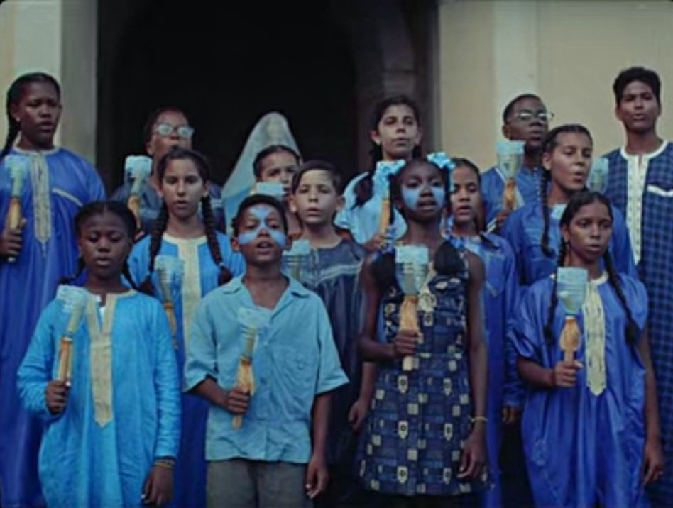 A chorus of young Cuban children of different racial backgrounds wear blue and sing with homemade candle holders.