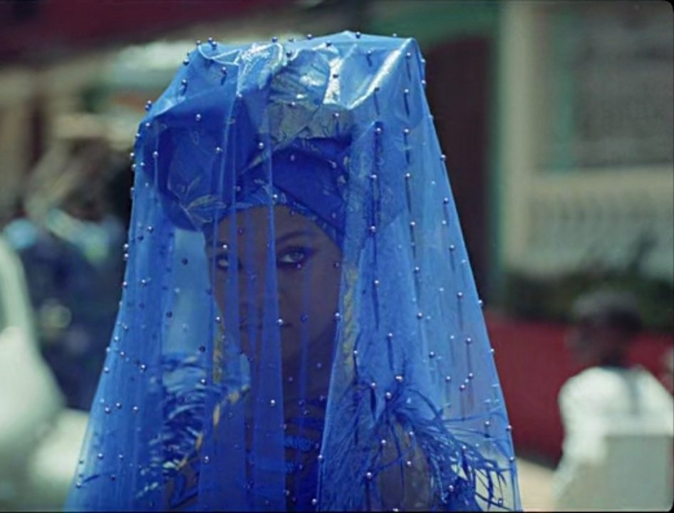 Rihanna as Deni's girlfriend Kofi. She wears a blue ornate dress with a blue turban and beaded veil.