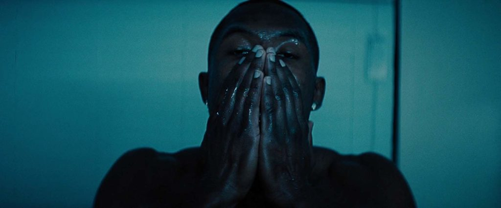 Adult Chiron washes his face in a bathroom bathed in teal-blue light.