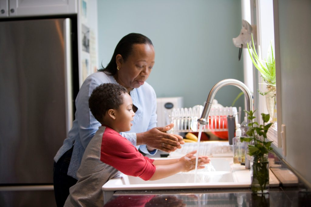 This African-American mother was shown in the process of teaching her young son how to properly wash his hands at their kitchen sink, briskly rubbing his soapy hands together under fresh running tap water, in order to remove germs, and contaminants, thereby, reducing the spread of pathogens, and the ingestion of environmental chemicals or toxins. Children are taught to recite the Happy Birthday song, during hand washing, allotting enough time to completely clean their hands. Keeping your hands clean is especially important during the COVID-19 outbreak.