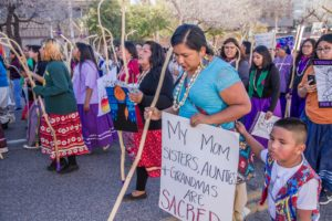 Indigenous Tohono Women led the Tucson 2019 Women's March with a show of strength, resilience and power. This woman's sign said: My Mom, Sisters, Aunties and Grandmas are sacred. Her son was by her side. International Women's Day