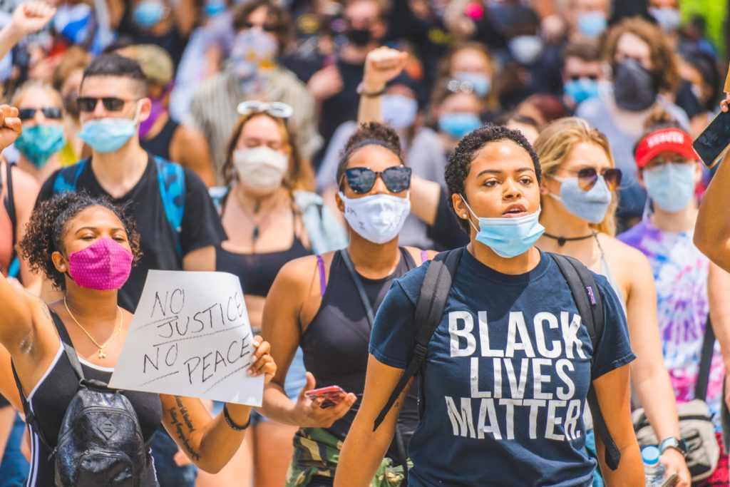 Picture of a revolution. A young woman wearing a mask and black lives matter t-shirt marching in a #BlackLivesMatter public demonstration in Cincinnati. Photo by Julian Wan on Unsplash
