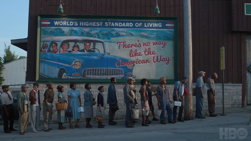 The two Americas, a line of Black men and women out of work standing in front of a billboard featuring a prosperous White family, as shown in Lovecraft Country. (Photo credit: HBO)