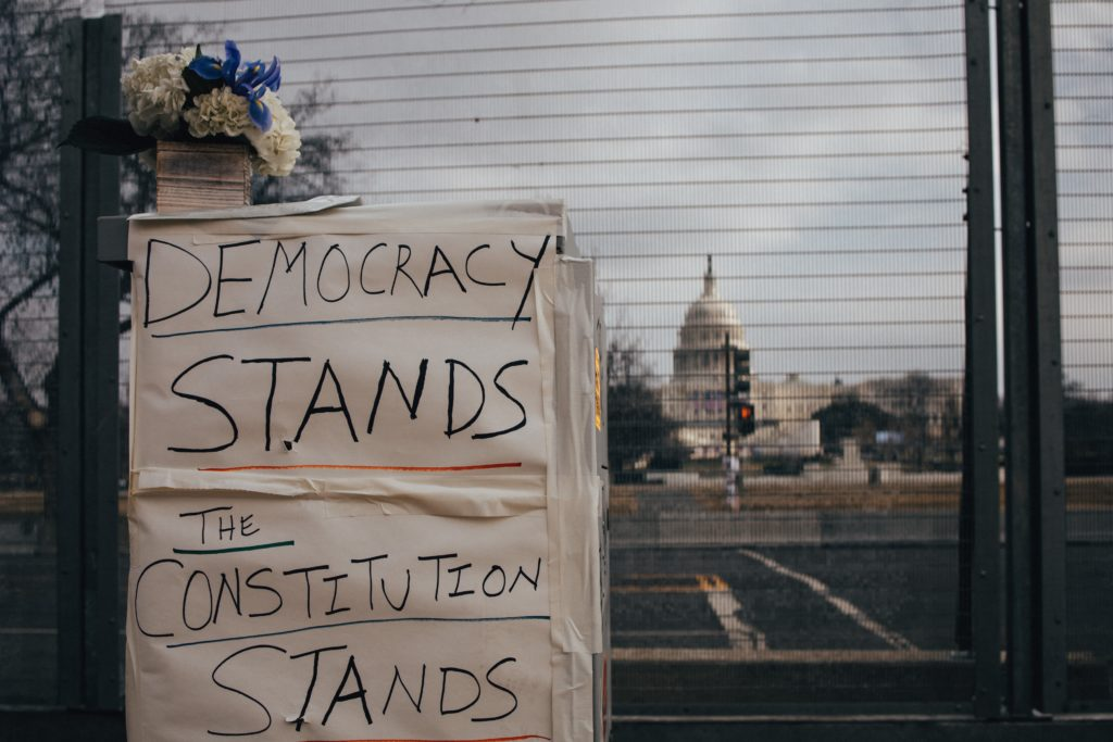 Sign in front of the Capitol Building, secured after January 6th insurrection. (Photo credit: Brendan Beale on Unsplash)